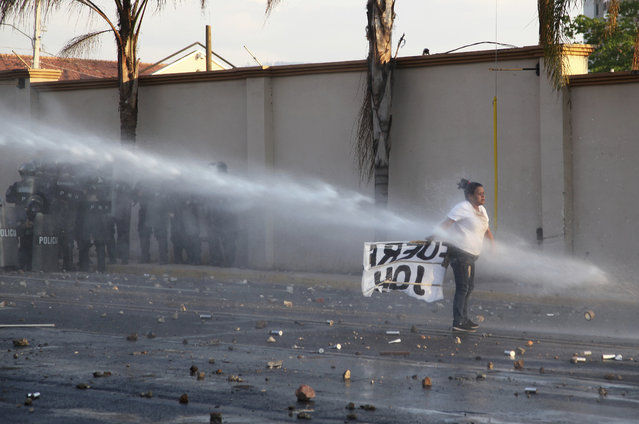 A supporters of opposition presidential candidate Salvador Nasralla is hit by a jet of water near the Presidential House in Tegucigalpa, Honduras, Friday, January 12, 2018. Following a disputed election marred by irregularities, incumbent President Juan Orlando Hernandez was declared the victor and will be inaugurated on Jan. 27. The opposition does not recognize Hernandez's victory and are protesting against the result. (Photo by Fernando Antonio/AP Photo)