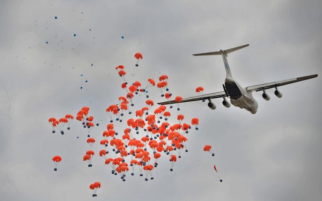 A Russian-made Ilyushin airlifter aircraft leased to the World Food Programme (WFP) makes a drop of food aid near a village in Ayod county, South Sudan, on February 6, 2020. The villagers hear the distant roar of jet engines before a cargo plane makes a deafening pass over Mogok, dropping sacks of grain from its hold to the marooned dust bowl below. South Sudan is the last place on earth where food is airdropped, and in Mogok there was little other choice: without the tonnes of grains and cereals, people would have simply perished. (Photo by Tony Karumba/AFP Photo)