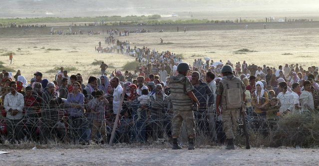 Turkish soldiers stand guard as Syrians wait behind the border fences near the southeastern town of Suruc in Sanliurfa province in this September 18, 2014 file photo. (Photo by Kadir Celikcan/Reuters)