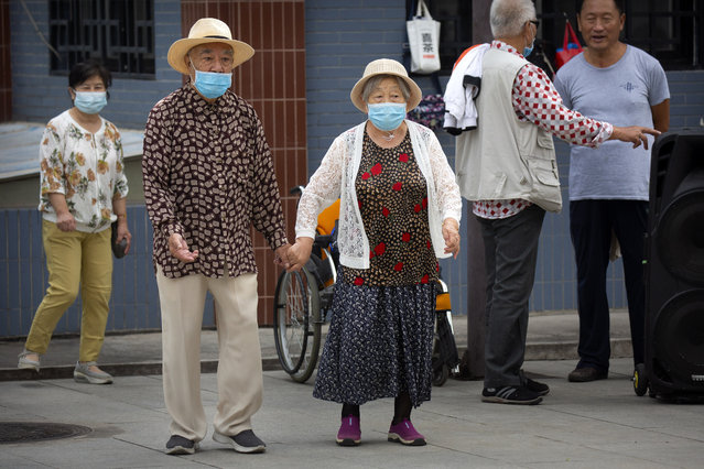 An elderly couple wearing face masks to protect against the coronavirus walks at a public park in Beijing, Saturday, September 12, 2020. Even as China has largely controlled the outbreak, the coronavirus is still surging across other parts of the world. (Photo by Mark Schiefelbein/AP Photo)