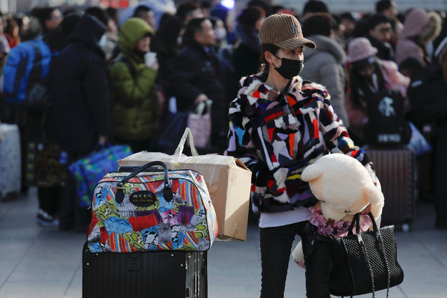 A passenger holds her luggage at the Beijing Railway Station as the annual Spring Festival travel rush begins ahead of the Chinese Lunar New Year, in central Beijing, China on February 1, 2018. (Photo by Damir Sagolj/Reuters)