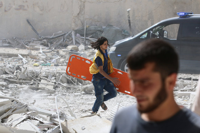 A man runs with a stretcher in a damaged site after airstrikes on the rebel held al-Qaterji neighbourhood of Aleppo, Syria September 21, 2016. (Photo by Abdalrhman Ismail/Reuters)