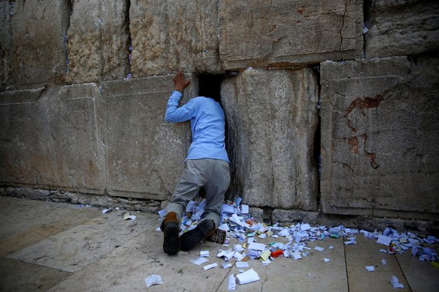 A man clears notes placed in the cracks of the Western Wall, Judaism's holiest prayer site, to clear space for new notes ahead of the Jewish New Year, in Jerusalem's Old City September 27, 2016. (Photo by Ronen Zvulun/Reuters)