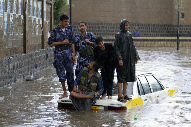 Policemen (L and 2nd L) stand on a car on a flooded street following heavy rains in Sanaa, Yemen, on March 20, 2013. (Photo by Mohamed al-Sayaghi/Reuters)
