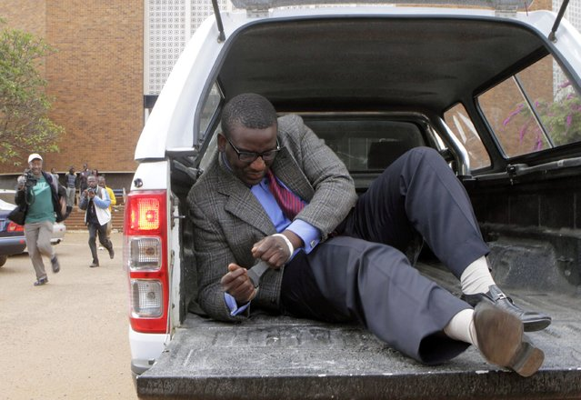 Editor of the state-run Sunday Mail newspaper Edmund Kudzayi gets out of a police vehicle as he arrives at the Harare Magistrates court, where he was charged with attempted terrorism, insurgency and banditry, in this June 21, 2014 file photo. (Photo by Philimon Bulawayo/Reuters)