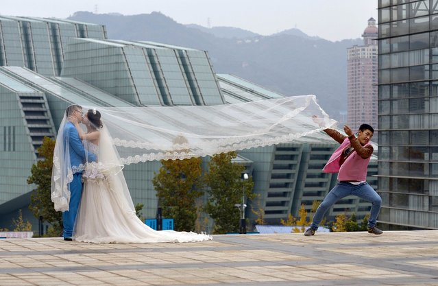 A newlywed couple kiss during a photo shoot, as an assistant runs away after lifting the veil, in Chongqing municipality, December 1, 2014. (Photo by Reuters/Stringer)