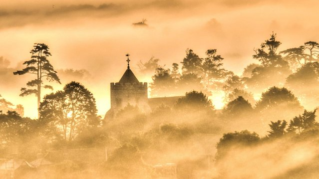 It was an ethereal start to the day on July 22, 2020 in Firle near Lewes, East Sussex, as morning mist was illuminated orange by the rising sun. (Photo by David Burr/Alamy Live News)