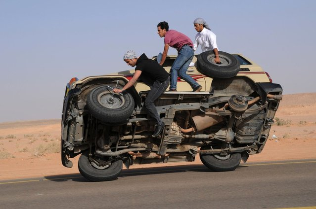 """Saudi youths demonstrate a stunt known as """"sidewall skiing"""" (driving on two wheels) in the northern city of Hail, in Saudi Arabia March 30, 2013. Performing stunts such as sidewall skiing and drifts is a popular hobby amongst Saudi youths. (Photo by Mohamed Al Hwaity/Reuters)"""