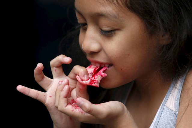 Alejandra Rodriguez, 8, eats a bloody nose made of gummy candy and red jelly at the Zombie Gourmet homemade candy manufacturer on the out skirts of Mexico City October 30, 2015. (Photo by Carlos Jasso/Reuters)