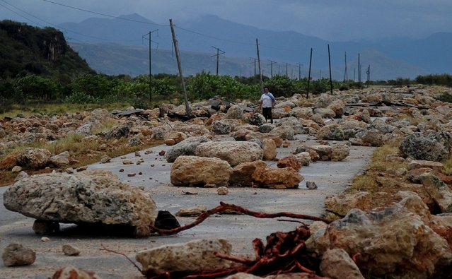 A woman walks on October 5, 2016 along a coastal road between Guantanamo and Baracoa which was left covered in rocks and severely damaged after the passage of Hurricane Matthew through the eastern tip of Cuba on Tuesday afternoon. Hurricane Matthew, the Caribbean's worst storm in nearly a decade, barreled towards the Bahamas Wednesday morning after killing nine people and pummeling Haiti and Cuba. (Photo by Yamil Lage/AFP Photo)