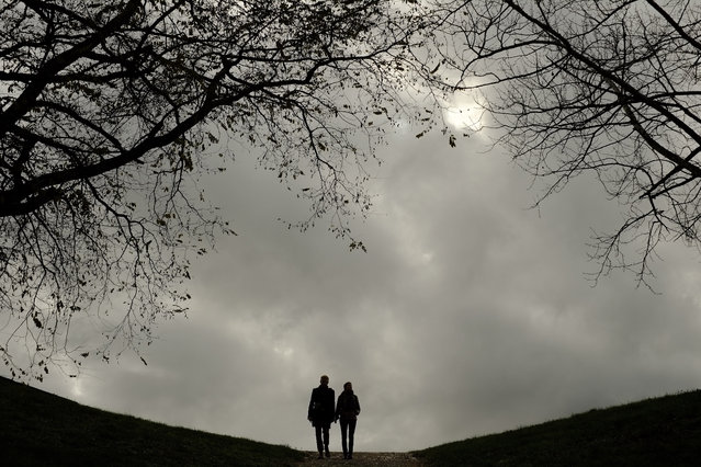 A couple go for a walk in Ciudadela Park on an autumn day, in Pamplona northern Spain, Wednesday, November 26, 2014. (Photo by Alvaro Barrientos/AP Photo)