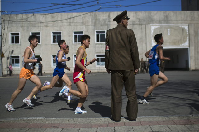 Marathon runners pass by a North Korean soldier during the race in Pyongyang on Sunday, April 14, 2013. North Korea hosted the 26th Mangyongdae Prize Marathon to mark the upcoming April 15, 2013 birthday of the late leader Kim Il Sung. (Photo by Alexander F. Yuan/AP Photo)
