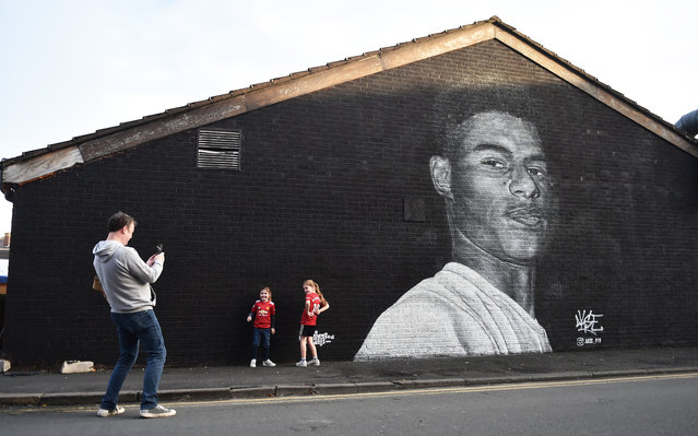 Two young girls pose for a photograph at a mural of Manchester United footballer Marcus Rashford, created by local street artist Akse, after the footballer received an MBE for his work campaigning for the government to provide meals to impoverished children on November 07, 2020 in Manchester, England. (Photo by Nathan Stirk/Getty Images)