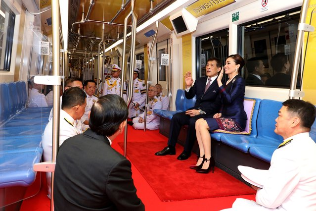 This photo taken on November 14, 2020 shows Thailand's King Maha Vajiralongkorn (2nd R) and Queen Suthida (R) riding with officials on an MRT commuter train during the inauguration of a new subway station in Bangkok. (Photo by Reuters/Stringer)