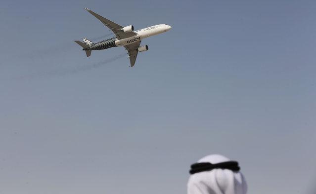 An Emirati man watches as an Airbus A350 XWB performs during the opening of the Dubai Airshow in Dubai, United Arab Emirates, Sunday, November 8, 2015. (Photo by Kamran Jebreili/AP Photo)