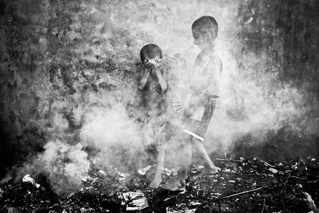 Two homeless street children were playing in the smoke created from burnt straws at Chittagong, Bangladesh. Suddenly dense smoke covered them and they were trying to protect themselves and escape. (Photo by Kazi Riasat Alve/2013 Sony World Photography Awards)