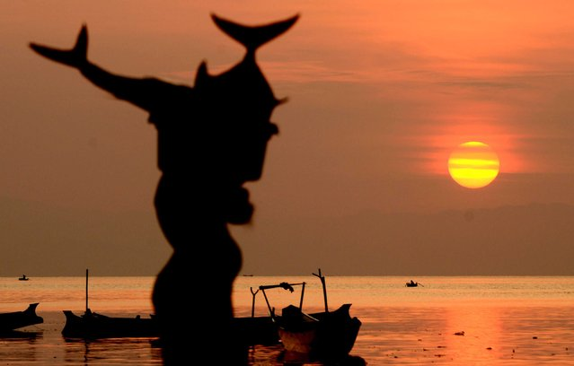 This picture taken on November 7, 2014 shows a vendor carrying fish as the sun rises near a traditional market in Tanjung Luar in Lombok, West Nusa Teggara. (Photo by Sonny Tumbelaka/AFP Photo)