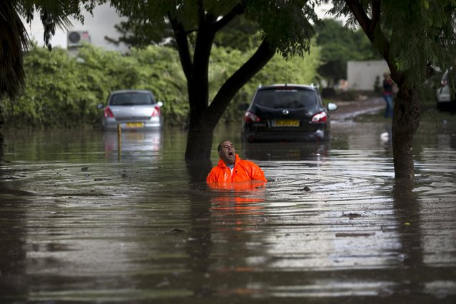 A municipality worker shouts as he tries to repair drainage on a flooded street in the southern city of Ashkelon, Israel, November 9, 2015. Vehicles were swept along the streets by torrents of rain in Ashkelon after 30 millimetres of rain struck the city in less than an hour, local media reported. Israeli police said they rescued several drivers from their vehicles and a few families who were trapped inside their homes. (Photo by Amir Cohen/Reuters)
