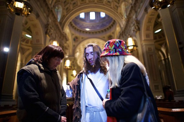 "(L-R) Christine Tyson and JoAnne Gilley pray with Michael Grant, 28, ""Philly Jesus"", inside Cathedral Basilica of Saints Peter and Paul in Philadelphia, Pennsylvania December 18, 2014. (Photo by Mark Makela/Reuters)"