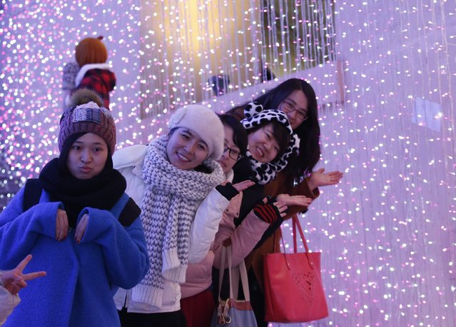Visitors pose for a picture in front of a light installation for Christmas celebrations in Beijing December 23, 2014. (Photo by Kim Kyung-Hoon/Reuters)