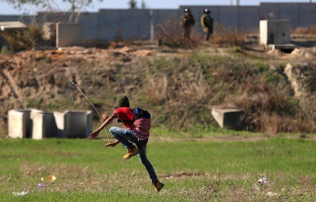 A Palestinian protester uses a sling to hurl stones at Israeli troops during clashes in the West Bank city of Tulkarm November 12, 2015. (Photo by Ahmad Talat/Reuters)