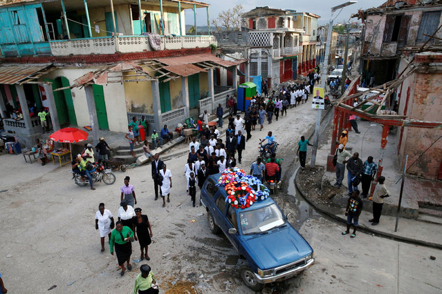 Relatives walk behind the hearse during the funeral of a woman who died during Hurricane Matthew in Jeremie, Haiti, October 18, 2016. (Photo by Carlos Garcia Rawlins/Reuters)