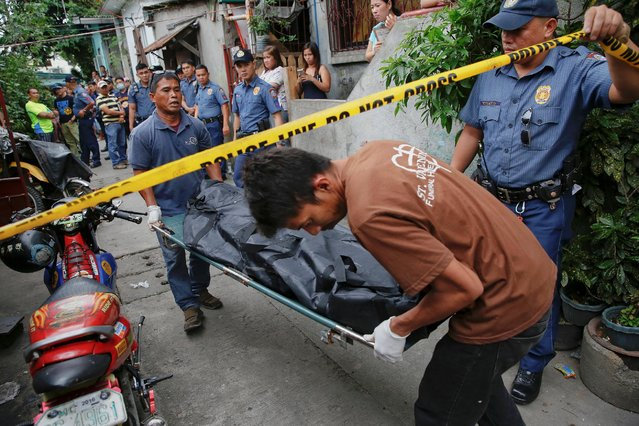A body is taken out of a house where two men were killed during a drugs related police operation in Manila, Philippines October 19, 2016. (Photo by Damir Sagolj/Reuters)