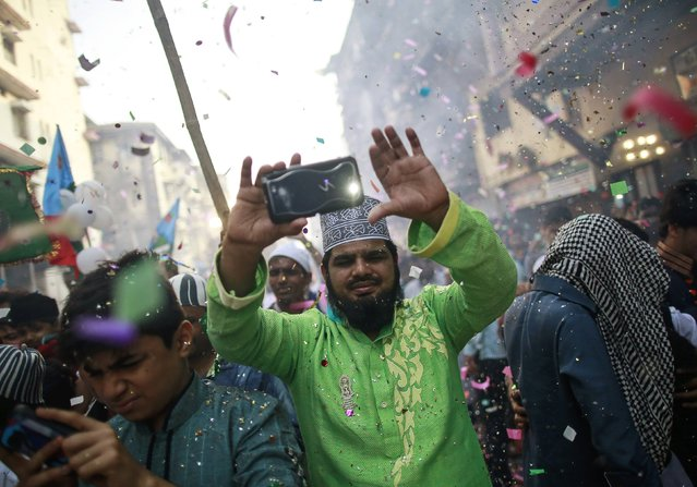 A man takes pictures as others fire confetti poppers while participating in a procession to mark Eid-e-Milad-ul-Nabi, or birthday celebrations of Prophet Mohammad, in Mumbai January 4, 2015. (Photo by Danish Siddiqui/Reuters)
