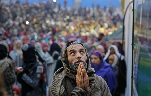 A Kashmiri devotee prays as a head priest displays a holy relic of Islam's Prophet Muhammed at the Hazratbal shrine on Eid-e-Milad, the birth anniversary of the Prophet, in Srinagar, India, Sunday, January 4, 2015. Thousands of Kashmiri Muslims gathered at the Hazratbal shrine which houses a relic believed to be a hair from the beard of the prophet. (Photo by Mukhtar Khan/AP Photo)