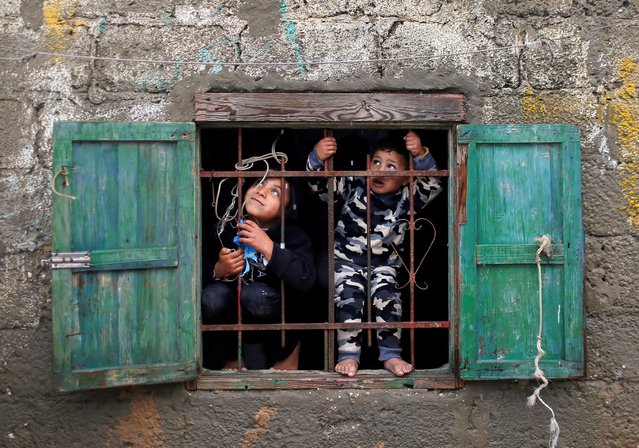 Palestinian children look out of their family's home window on a rainy day at Deir al-Balah refugee camp in the central Gaza Strip on December 17, 2020. (Photo by Mohammed Salem/Reuters)