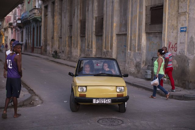 People ride in a Polski Fiat vehicle in downtown Havana January 4, 2015. Picture taken January 4, 2015. (Photo by Alexandre Meneghini/Reuters)