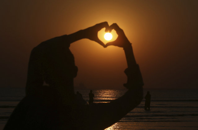 A boy make heart sign while the last sunset of 2020 hangs over the Sindh's provincial capital of Karachi, Pakistan, Thursday, December 31, 2020. (Photo by Fareed Khan/AP Photo)