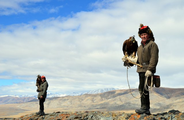 Eagle hunters Ushkish, at right, and Berik prepared to hunt atop a mountain. (Photo by Brad Ruoho/The Star Tribune)