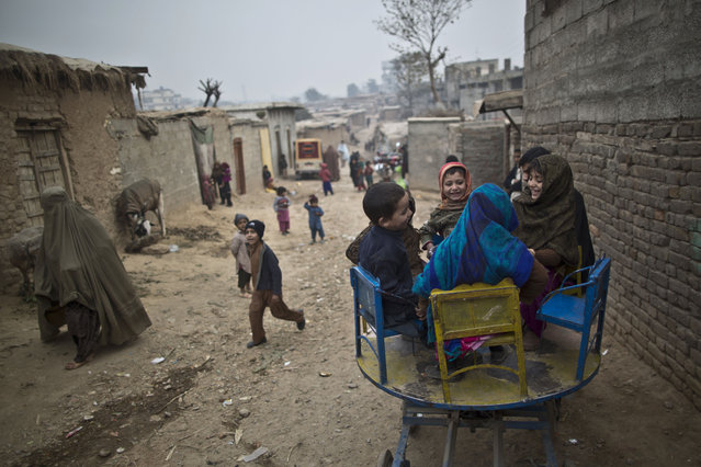 Pakistani children who were displaced with their families from Pakistan's tribal areas enjoy a ride on a hand-operated wheel for the price of 5 rupees, (5 U.S. cents) for 5 minutes,  in a poor neighborhood on the outskirts of Islamabad, Pakistan, Tuesday, Dec. 30, 2014. (AP Photo/Muhammed Muheisen)