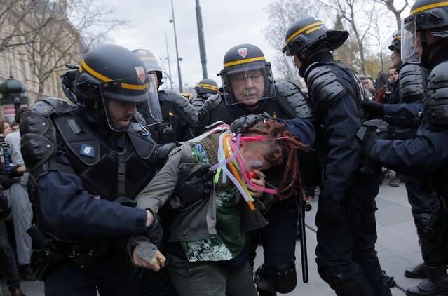 Policemen detain an activist during a protest ahead of the 2015 Paris Climate Conference, in Paris, Sunday, November 29, 2015. (Photo by Christophe Ena/AP Photo)