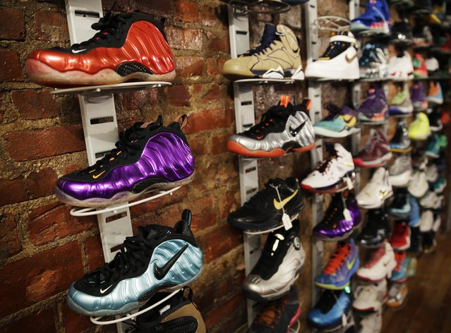 In this January 12, 2015 photo, a wall of collectable sneakers are displayed at Sneaker Pawn in the Harlem section of New York. Along with his father, a 16-year-old sneaker-loving teen is using high end athletic footwear their pawn shop as collateral. (Photo by Seth Wenig/AP Photo)