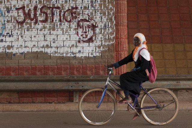 "A girl rides a bicycle past graffiti reading ""Justice"" with a picture of slain ex-President Thomas Sankara in Ouagadougou, Burkina Faso, December 4, 2015. (Photo by Joe Penney/Reuters)"