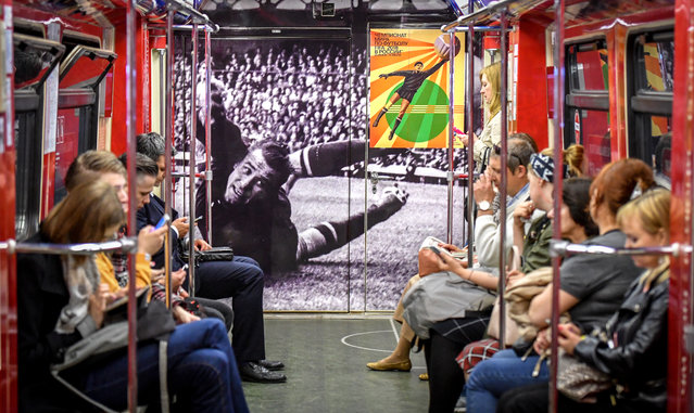 Commuters ride a World Cup themed metro car decorated with a picture of Soviet goalkeeper Lev Yashin in Moscow on June 13, 2018, ahead of the Russia 2018 World Cup football tournament. (Photo by Yuri Kadobnov/AFP Photo)