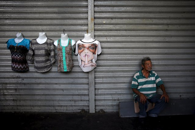 A man sells clothes on the street, in the Caracas downtown December 4, 2015. (Photo by Nacho Doce/Reuters)