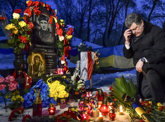 """Ukraine's President Petro Poroshenko attends a wreath laying ceremony at the monument to the fallen Mikhail Zhiznevsky from the so-called """"Heavenly Sotnya"""" (Hundred) on the Day of Unity in Kiev, January 22, 2015. Mikhail Zhiznevsky and Serhiy Nigoyan were the first two demonstrators who were killed during the EuroMaidan protests a year ago, according to local media. (Photo by Mykola Lazarenko/Reuters/Ukrainian Presidential Press Service)"""