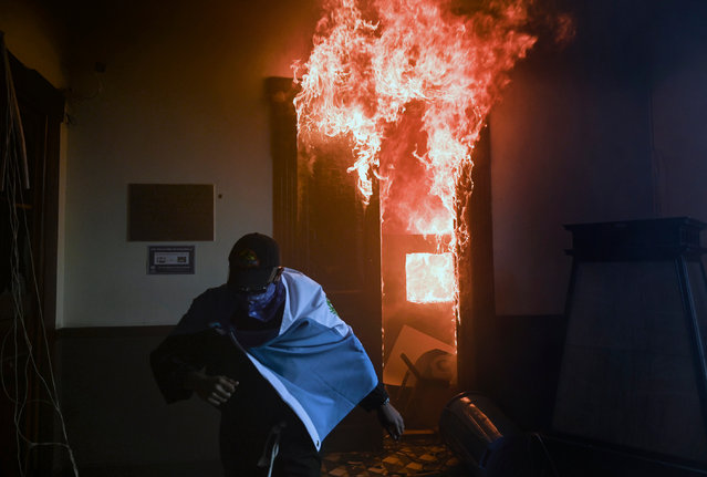 """A demonstrator runs after setting on fire an office of the Congress building during a protest demanding the resignation of Guatemalan President Alejandro Giammattei, in Guatemala City on November 21, 2020. The Vice President of Guatemala, Guillermo Castillo, asked President Alejandro Giammattei to resign together for """"the good of the country"""", after the 2021 budget -the largest in history, which generates indebtedness and rejection among Guatemalans- was approved in Congress. (Photo by Johan Ordóñez/AFP Photo)"""