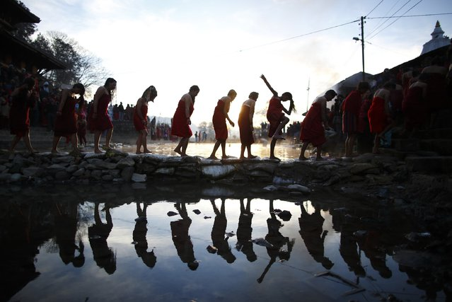 A devotee loses her balance as she crosses the Triveni River along with her friends after taking a holy bath during the Swasthani Bratakatha festival in Panauti near Kathmandu January 24, 2015. (Photo by Navesh Chitrakar/Reuters)