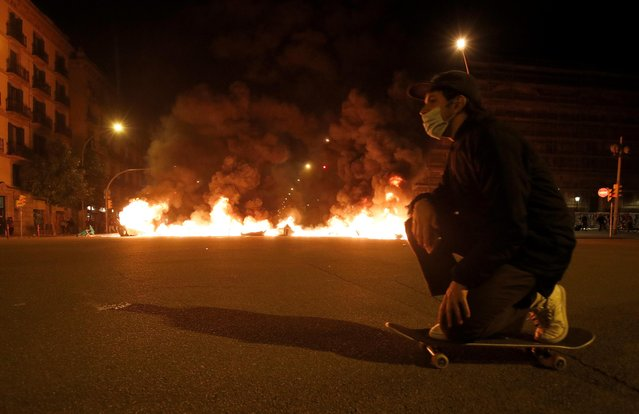 A man kneels on a skateboard in front of a burning barricade during a protest in support of Catalan rapper Pablo Hasel, after he was given a jail sentence on charges of glorifying terrorism and insulting royalty in his songs, in Barcelona, Spain, February 19, 2021. (Photo by Albert Gea/Reuters)