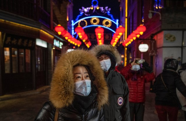 People walk down an alleyway decorated with red lanterns, or hong denglong, during the Chinese New Year holiday, also known as the Spring Festival, ushering in the Year of the Ox, at a commercial and tourist area on February 16, 2021 in Beijing, China. Although they have been contained, recent outbreaks in the capital and across northern China have prompted the government to cancel most Lunar New Year celebrations nationwide and people have been urged to forego travel during the holiday period which typically sees hundreds of millions move between cities and villages to visit family. (Photo by Kevin Frayer/Getty Images)