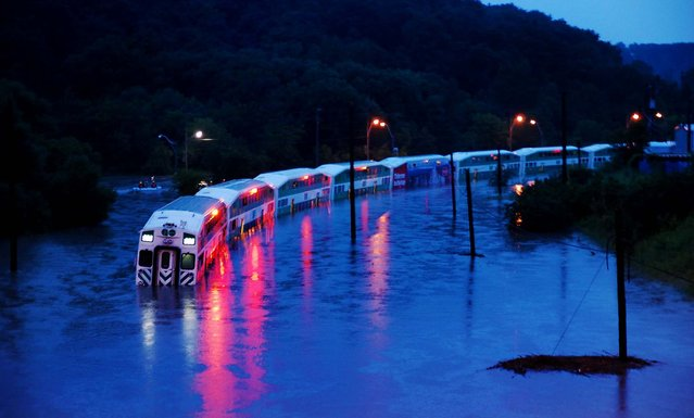 A GO Train is stranded on flooded tracks in Toronto, on July 8, 2013. A severe thunderstorm forced the shutdown of Toronto's subways, cut power to 300,000 in Canada's largest city and caused Porter Airlines to cancel all flights out of the downtown airport Monday evening. (Photo by Winston Neutel/The Canadian Press)