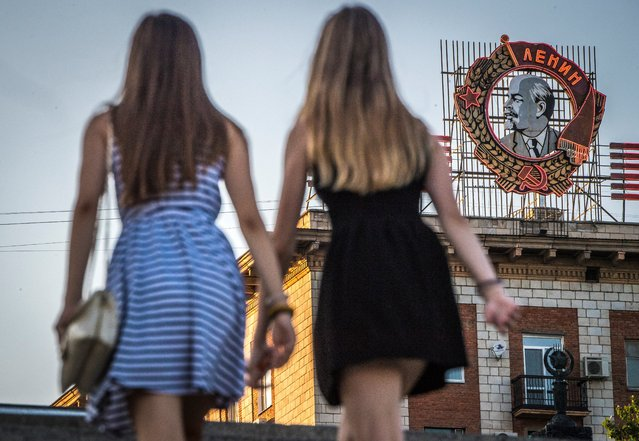 A photo taken on August 21, 2017 shows girls passing in front of a building with a display of the Soviet state founder Vladimir Lenin Order in Volgograd. Volgograd Arena will host several cames of the FIFA World Cup 2018. (Photo by Mladen Antonov/AFP Photo)
