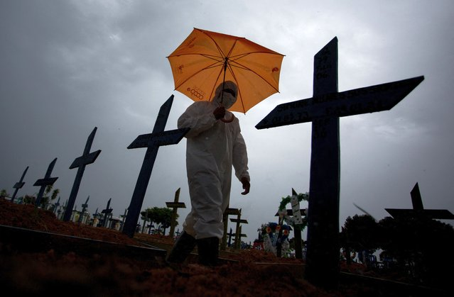 A workers wearing a protective suit and carrying an umbrella walks past the graves of COVID-19 victims at the Nossa Senhora Aparecida cemetery, in Manaus, Brazil, on February 25, 2021. Brazil surpassed 250,000 deaths due to COVID-19. (Photo by Michael Dantas/AFP Photo)