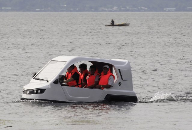 """Engineers test-drive a gasoline-powered """"Salamander"""", an amphibious tricycle, at Taal lake in Batangas city, south of Manila January 28, 2015. The """"Salamander"""", invented by H20 Technologies, is capable of travelling on both land and water and can be used for rescue operations when there is flooding. The gasoline-powered version can carry five passengers and would cost around 200,000 Philippine pesos ($4500). (Photo by Romeo Ranoco/Reuters)"""
