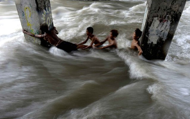 "Children swim in a swollen creek under a flyover in Manila on December 19, 2015. Heavy rains pummelled the entire Philippines on December 19, flooding more areas as the government declared a ""state of national calamity"". (Photo by Noel Celis/AFP Photo)"