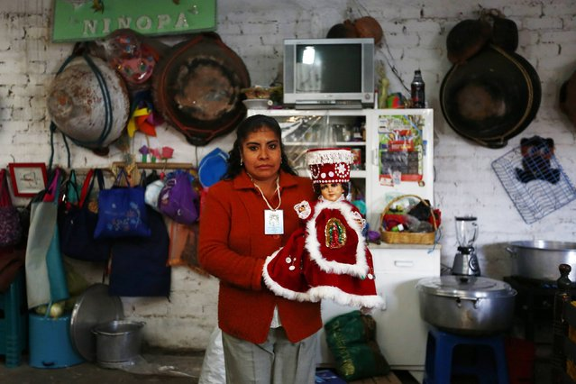 A woman poses for a photograph while holding a dressed-up doll representing baby Jesus during a celebration 40 days after the birth of Jesus inside her house in Xochimilco, on the outskirts of Mexico City, February 2, 2015. (Photo by Edgard Garrido/Reuters)
